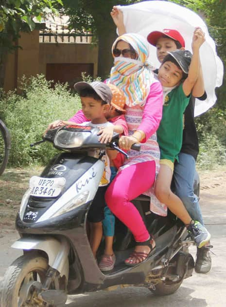 People cover their faces to protect themselves from scorching heat on a very Hot Day in Allahabad.