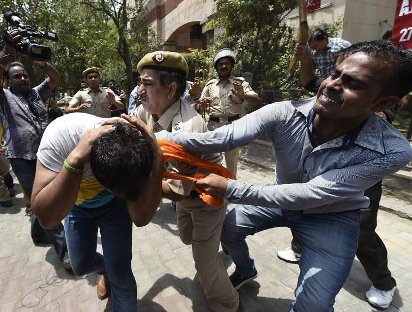 A policeman intervene as BJP and CPI workers clash during BJP protest outside the CPI(M) headquarters, damaged their signboard in protest against the murder of a party worker allegedly by Left party supporters in Kerala, in New Delhi.