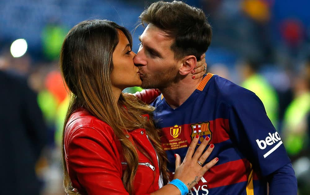 Barcelona's Lionel Messi kisses his wife Antonella Roccuzzo as they celebrate after winning the final of the Copa del Rey soccer match between FC Barcelona and Sevilla FC at the Vicente Calderon stadium in Madrid.