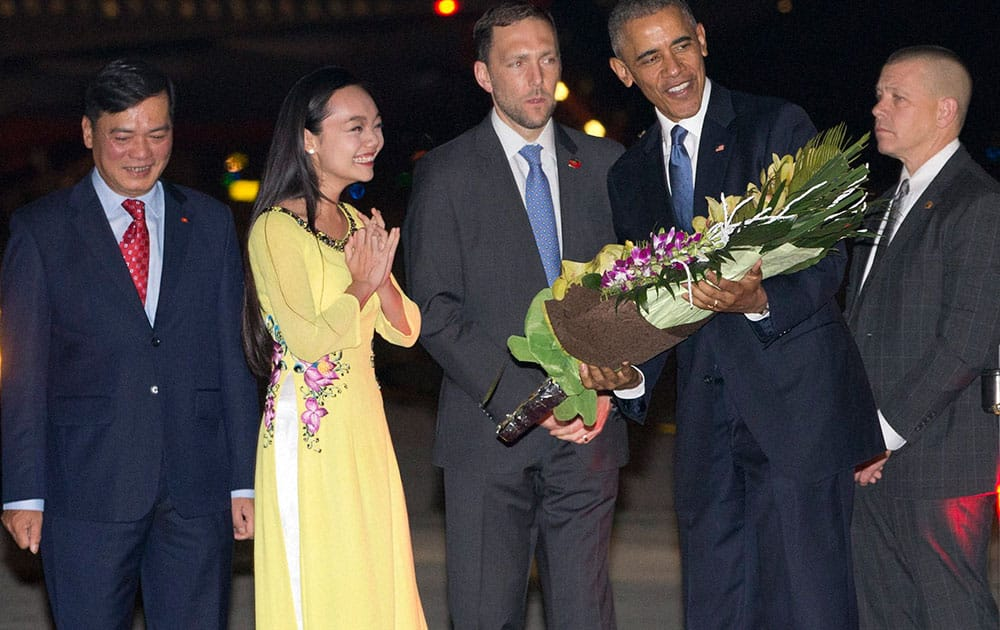 U.S. President Barack Obama is given flowers by Linh Tran, the ceremonial flower girl, as he arrives on Air Force One at Noi Bai International Airport in Hanoi, Vietnam.