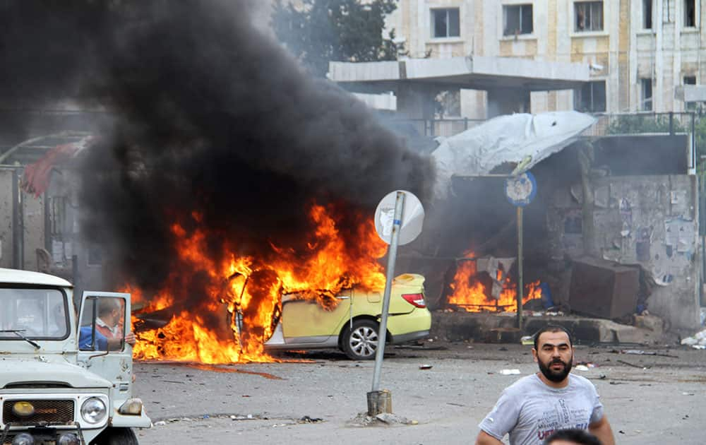 Syrians gather in front of a burning car at the scene where suicide bombers blew themselves up, in the coastal town of Tartus, Syria.