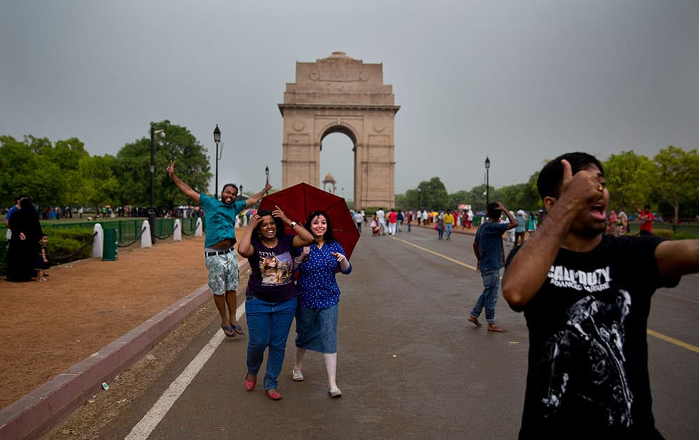 People enjoy a sudden rain and thunderstorm at the India Gate in New Delhi. After days of relentless summer heat, storm accompanied by short spells of rain brought relief to the Indian capital.