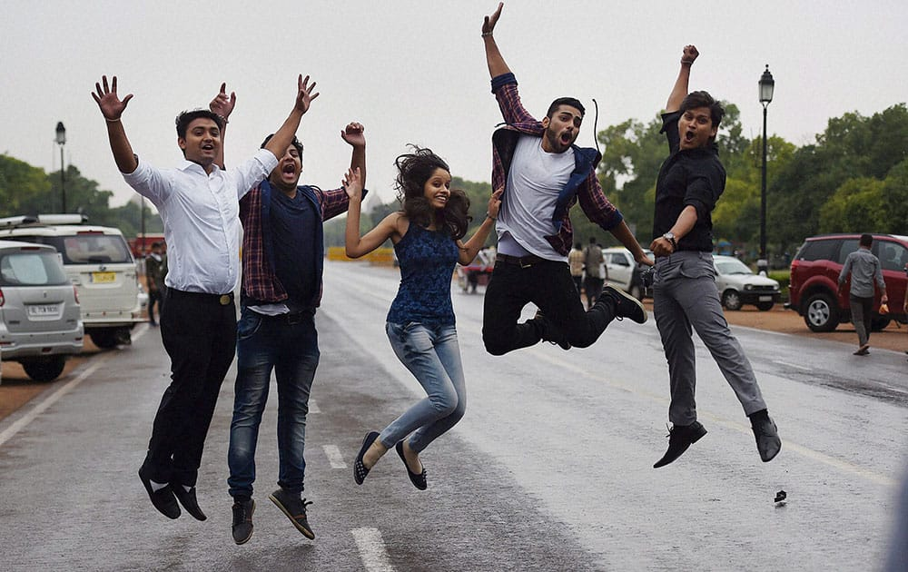 Youngsters enjoy in the rains in New Delhi.