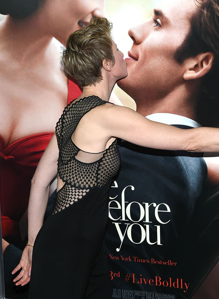 Director Thea Sharrock kisses a poster of Sam Claflin and Emilia Clarke at the world premiere of