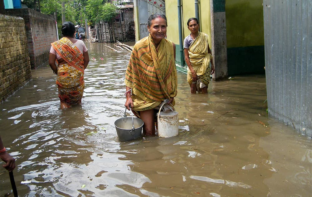 People wade through a waterlogged locality after heavy rains at Balurghat in South Dinajpur district of West Bengal.