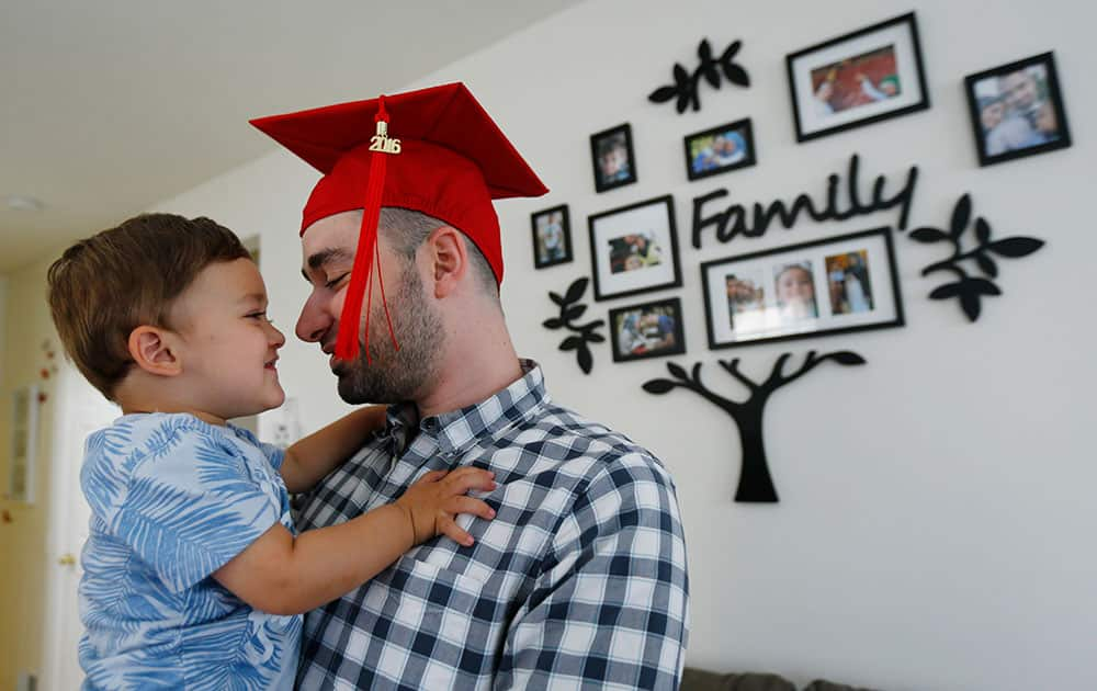 Mohamad Bassel Khair, right, kisses his 2-year-old son Sami Khair between a photo shoot with The Associated Press in his home in Clifton, N.J. Khair, of Damascus, Syria, is graduating from Montclair State University with a master's degree in nutrition and food science.