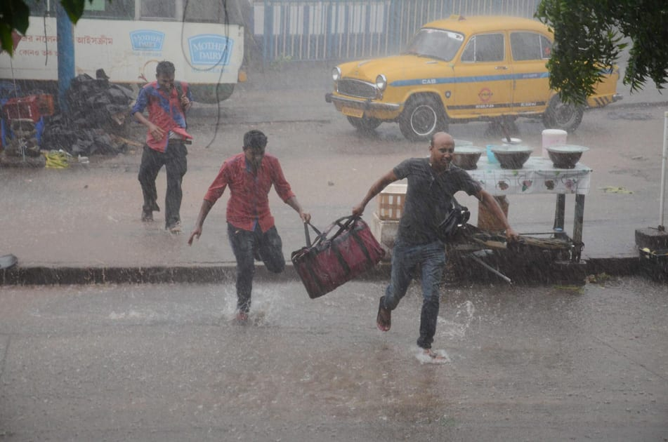 People, holding their bags, run to find a shed as it rains in Kolkata.