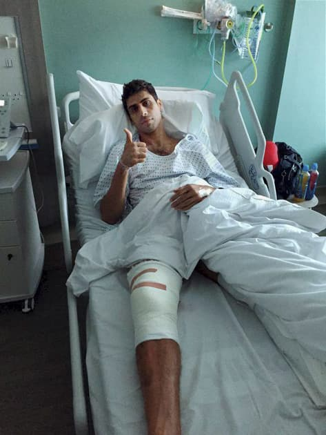 Seamer Ashish Nehra gestures after undergoing a surgery on his right knee in London.