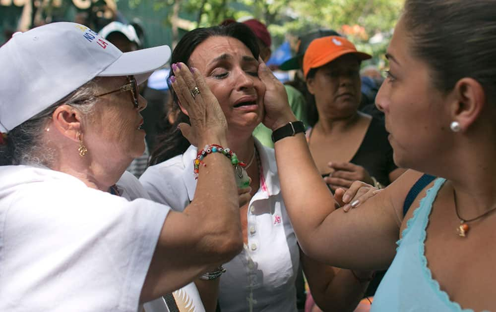 Two woman comfort another who became visibly upset over her country's turmoil during a demonstration demanding the government pursue a referendum to recall President Nicolas Maduro, in Caracas, Venezuela.