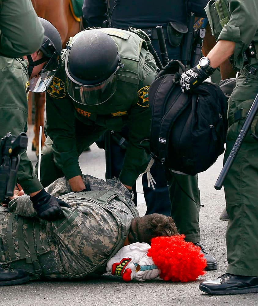 Orange County Sheriff's deputies take a demonstrator into custody who had been wearing a clown mask during a protest outside a rally for Republican presidential candidate Donald Trump at the Anaheim, Calif., Convention Center.
