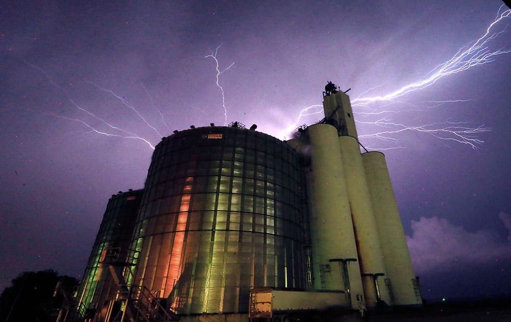 Lightning from a severe storm fills the sky behind a grain elevator in Belvue, Kan. The storm produced tornadoes near Chapman, Kan.