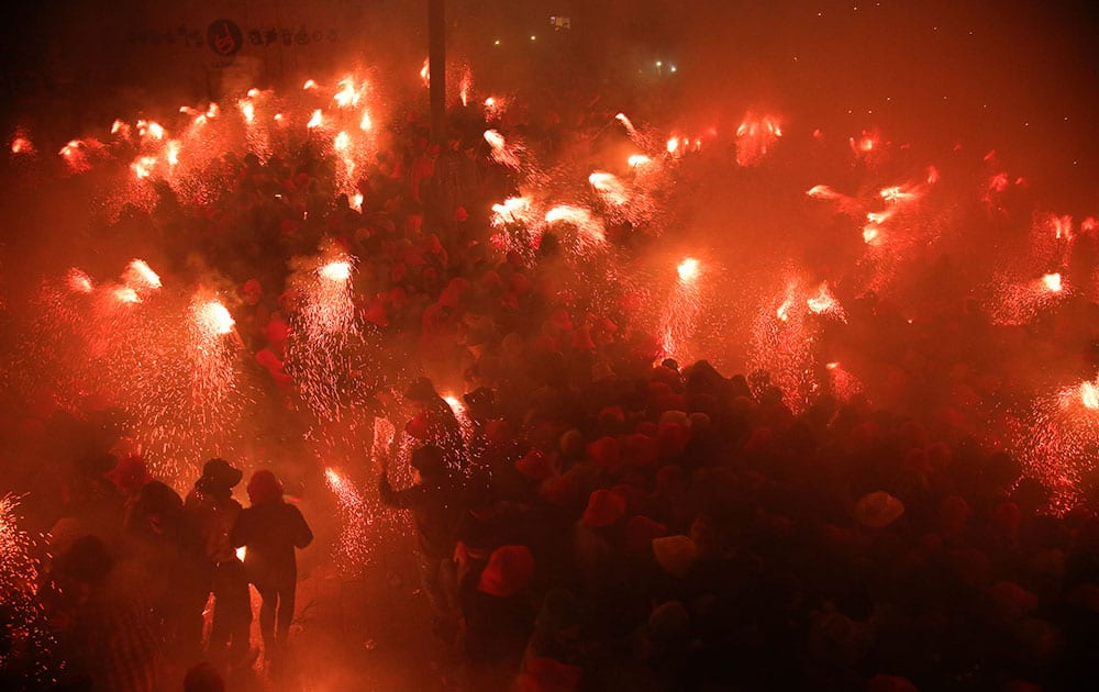 Revellers burn flares as they take part in the Patum in the Catalan village of Berga, Spain.