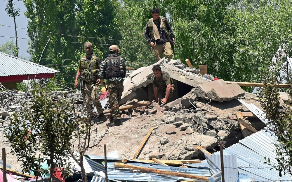 Security jawans search the debris of a house after encounter with militants at Khonchipora village in Tangmarg, in District Baramulla of North Kashmir.