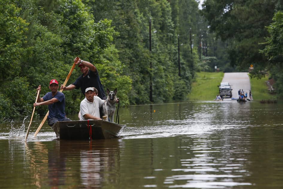 Roland Courville steers a boat across Mill Creek Road as he helps people escape from a neighborhood cut off by a flooded Spring Creek.