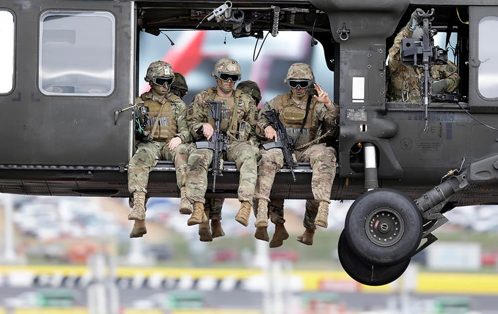 A U.S. Army repel team with the 82nd Airborne Division rides in a Black Hawk helicopter over Charlotte Motor Speedway during military appreciation exercises prior to the NASCAR Sprint Cup Series auto race at the in Concord, N.C.