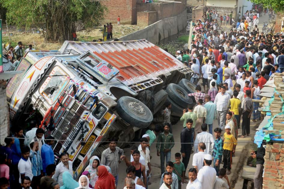 People gather near the truck which rammed into a house in Thakurganj area in Lucknow.