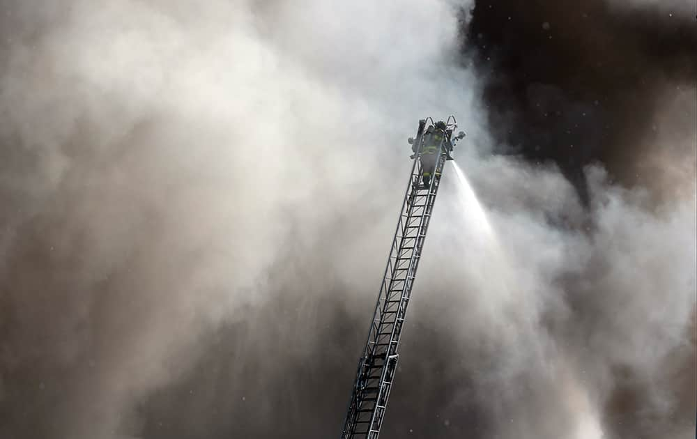 A firefighter on an aerial ladder tries to put out a fire following an explosion in a scrap pile at All Metals Recycling in Madison, Wis.