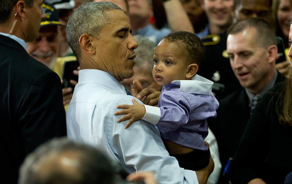 President Barack Obama carries a infant in his arms while greeting members of the audience after speaking at Concord Community High School in Elkhart, Ind.