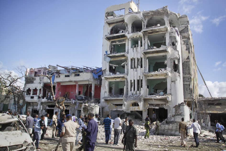 Security forces examine the scene after a bomb attack on Ambassador Hotel in Mogadishu, Somalia.