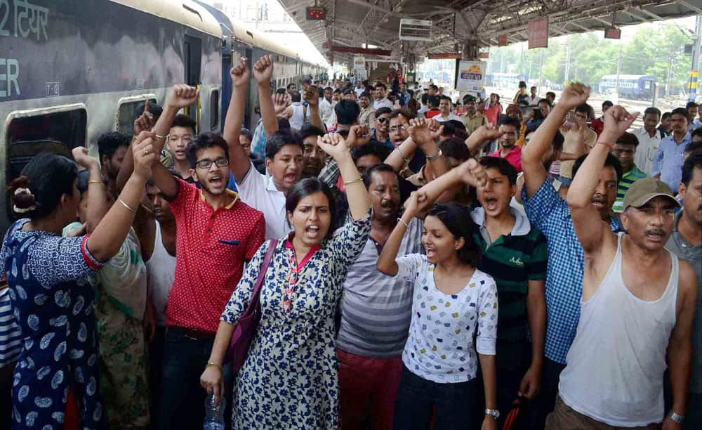 Angry passengers shout slogans against dysfunctioning of air conditioners inside the West Bengals Sampark Kranti Express train at Allahabad Railway station.