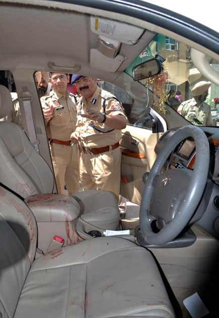 Police officers during investigation at the car of garment trader Anil Kumar who was shot dead in the vehicle in Jalandhar.