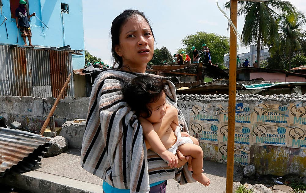 A mother carries her child as she walks away from her shanty home as demolition teams remove her makeshift community at suburban Quezon city northeast of Manila, Philippines.