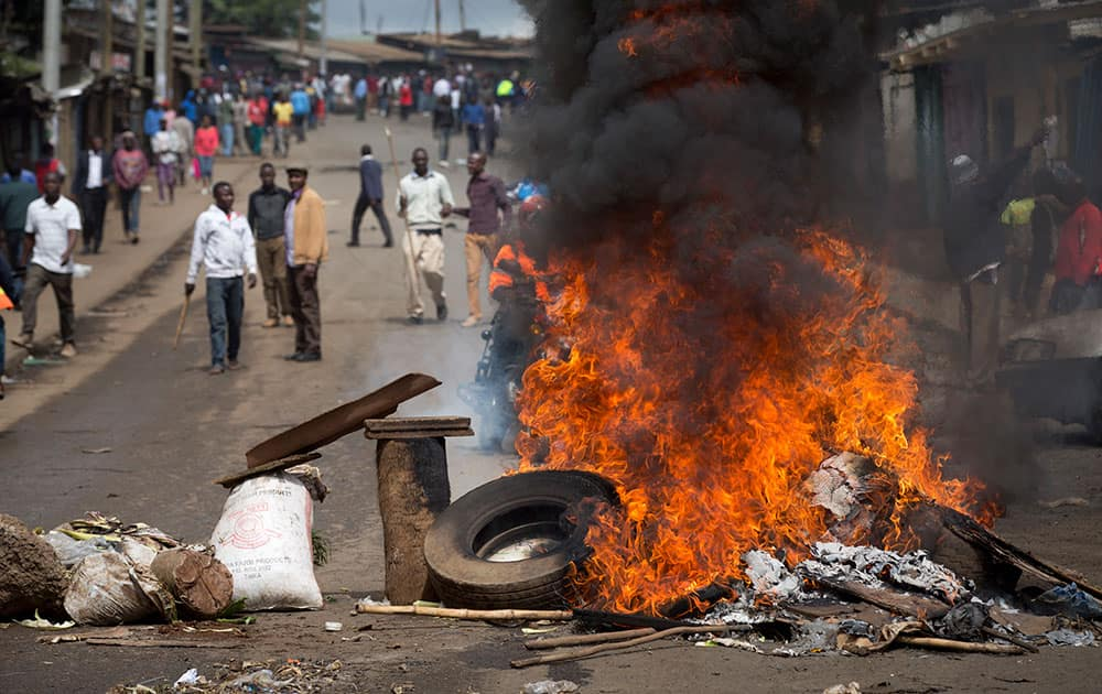Protesters carrying sticks and rocks stand behind a barricade of burning tyres in Nairobi, Kenya