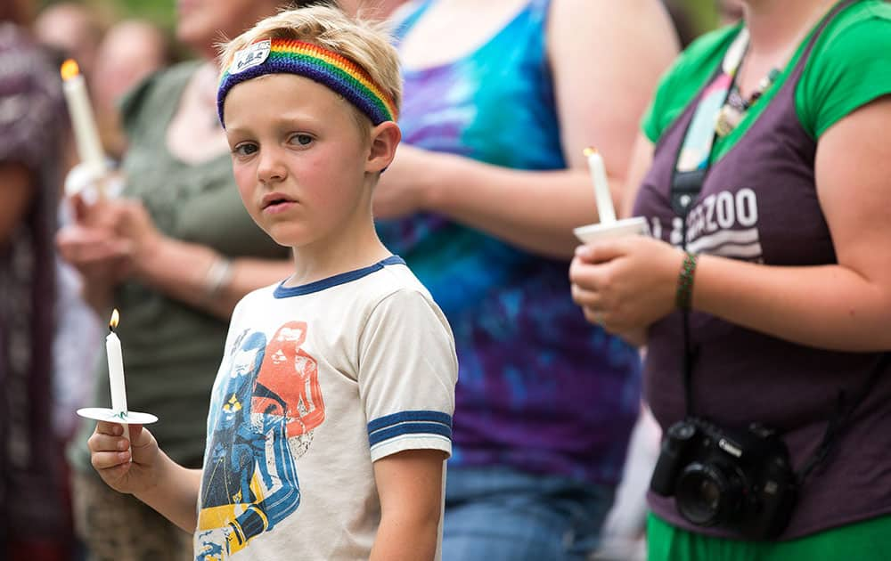 Emerson Wyzgoski, 7, of Kalamazoo, holds a candle at a candlelight vigil at Bronson Park