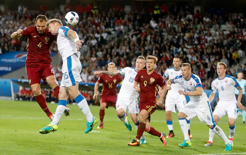 Russia's Sergei Ignashevich, left, and Slovakia's Tomas Hubocan go for an header during the Euro 2016