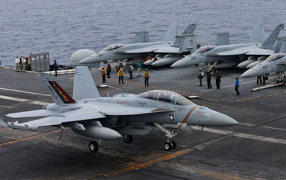 An F/A-18 Hornet lands on the deck of the nuclear-powered aircraft carrier the USS John C.
