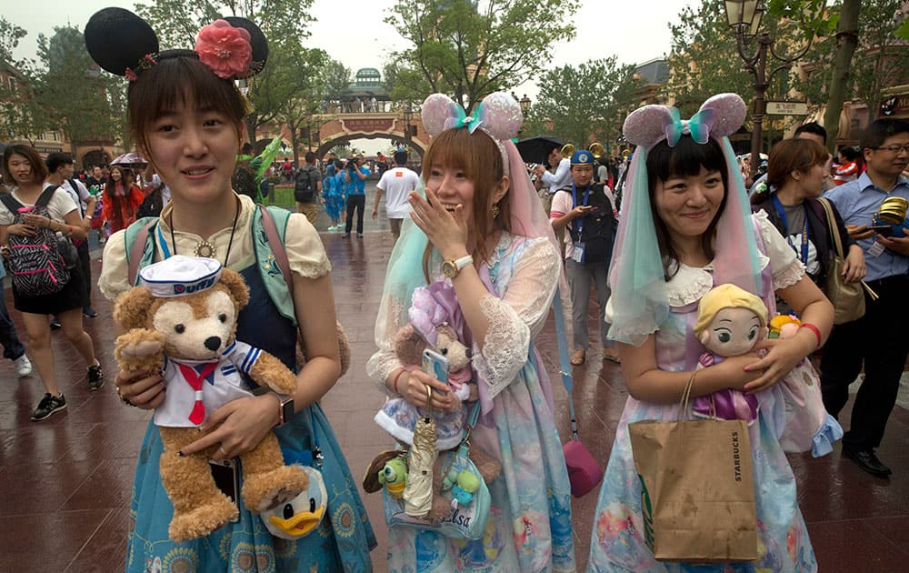 Visitors dress up as they attend the opening day of the Disney Resort in Shanghai.