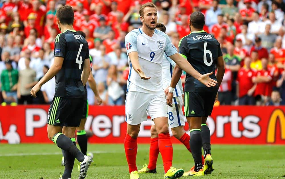 England's Harry Kane, center, calls for referee's attention as Wales' Ben Davies, left, and Wales' Ashley Williams stand beside him, during the Euro 2016