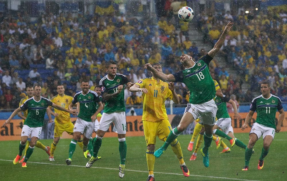 Northern Ireland's Aaron Hughes, center right, jumps for the ball during the Euro 2016
