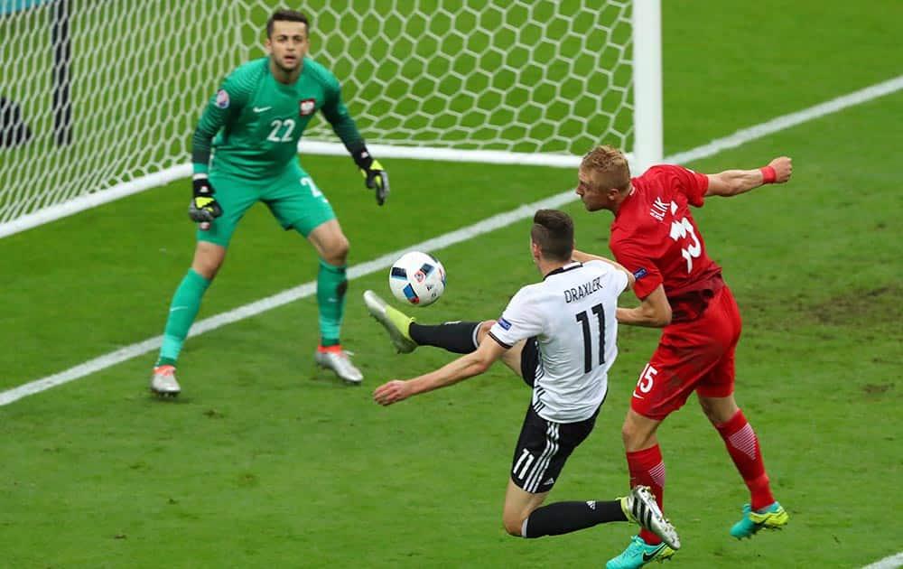 Poland goalkeeper Lukasz Fabianski looks on as Germany's Julian Draxler and Poland's Kamil Glik