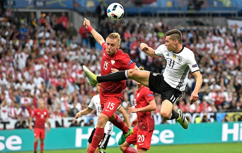 Poland's Kamil Glik, jumps for the ball with Germany's Julian Draxler during the