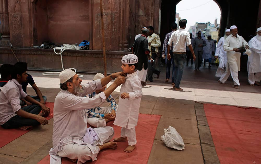 A Muslim man grooms a young boy as they wait to offer prayers