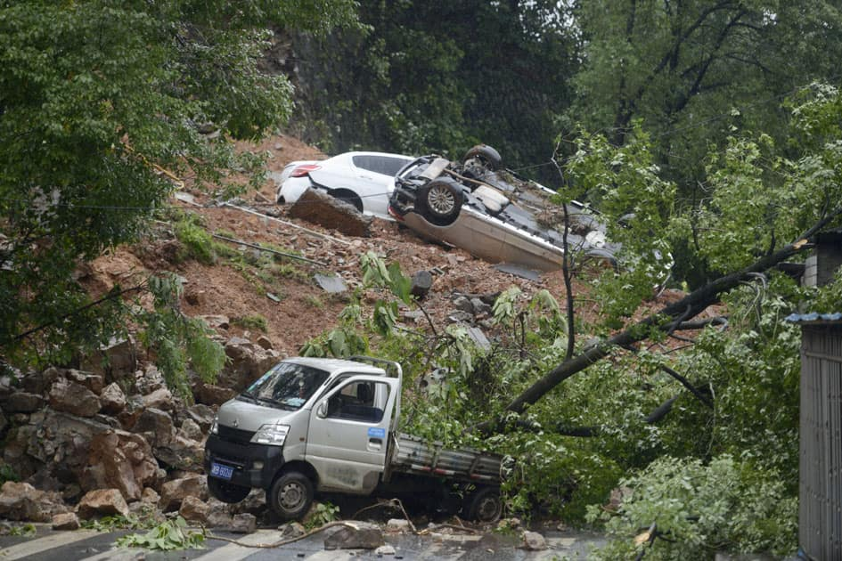 damaged vehicles are stuck on a section of road blocked by a landslide
