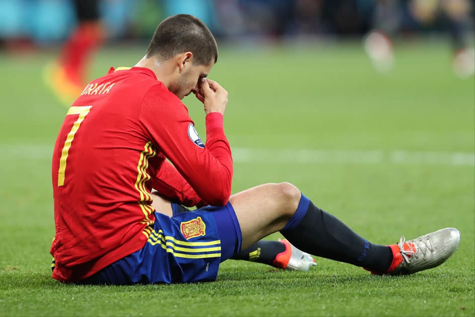 Alvaro Morata sits on the pitch during soccer match