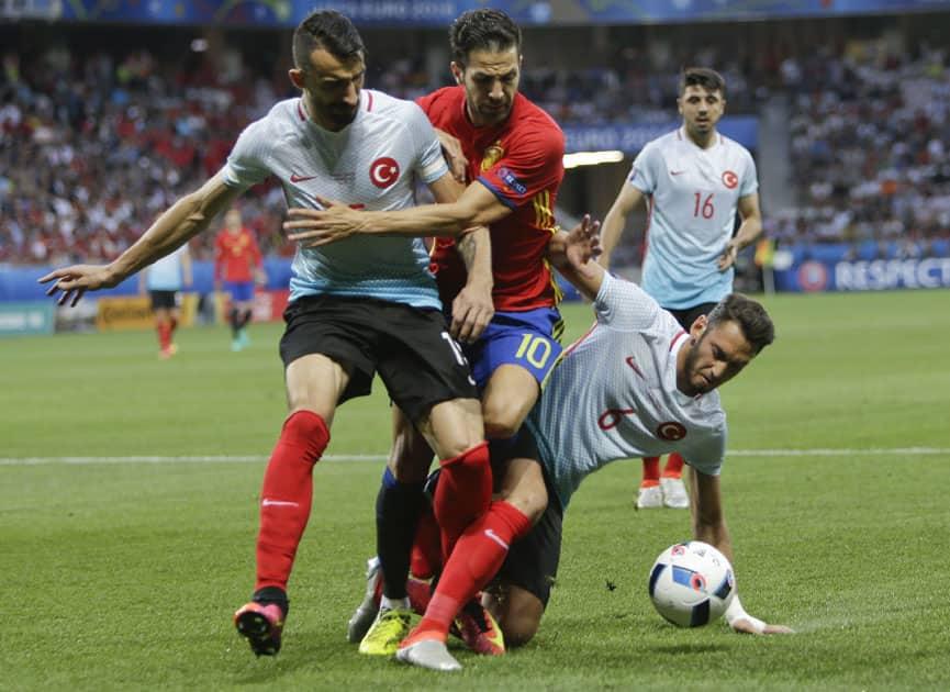 Turkey's Mehmet Topal, Spain's Cesc Fabregas and Turkey's Hakan Calhanoglu fight for the ball