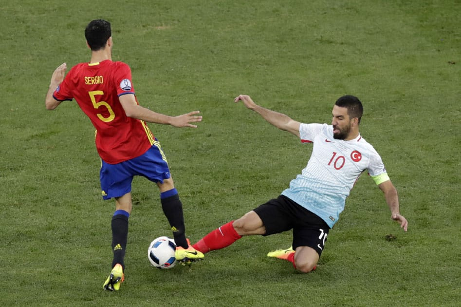Cesc Fabregas is tackled by Turkey's Arda Turan