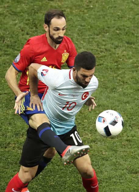 Arda Turan fights for the ball against Spain's Juanfran