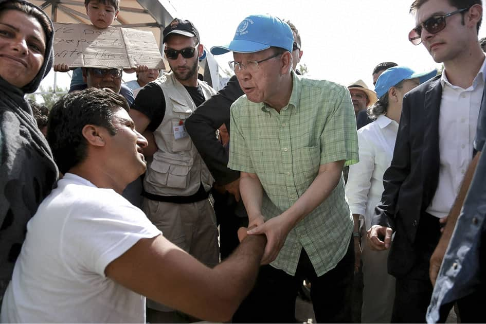 U.N. Secretary General Ban Ki-moon, center, greets a refugee