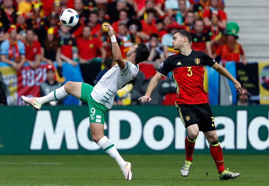 Belgium's Thomas Vermaelen, right, watches Ireland's Shane Long reach for the ball