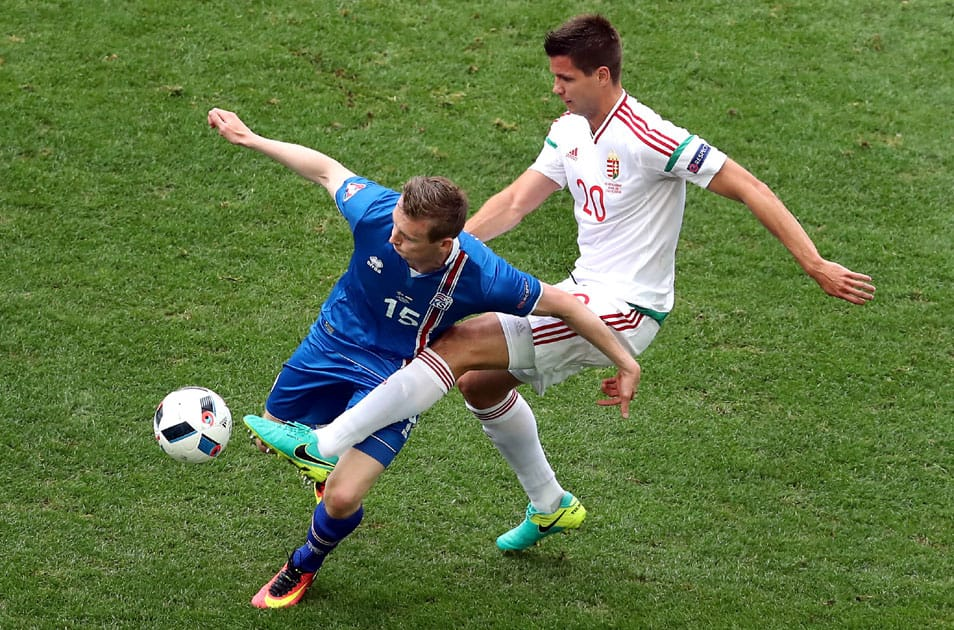 Iceland's Jon Dadi Bodvarsson, left, and Hungary's Richard Guzmics, right, challenge for the ball