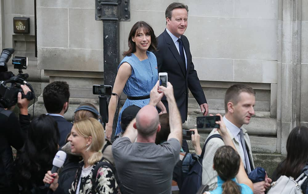British Prime Minister David Cameron and his wife Samantha leave after casting their votes
