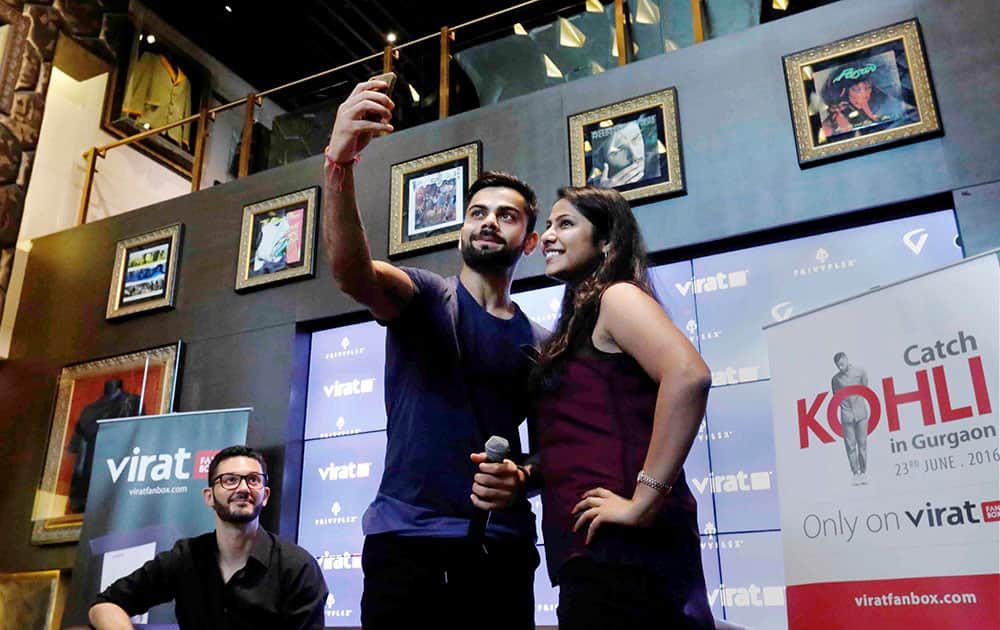 Cricketer Virat Kohli takes selfie with a fan at an event