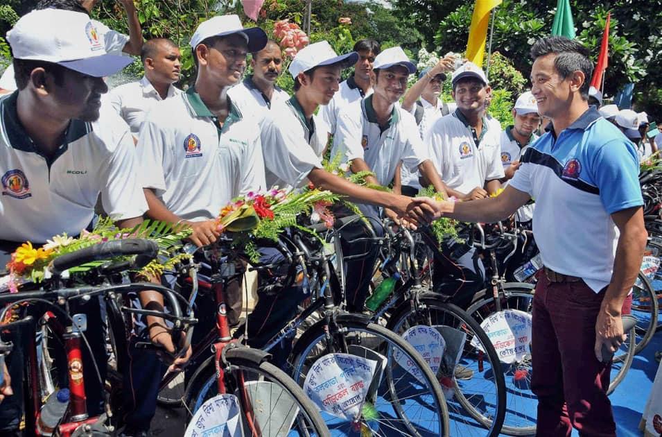 Former football captain Baichung Bhutia shakes hands with the youth cyclists