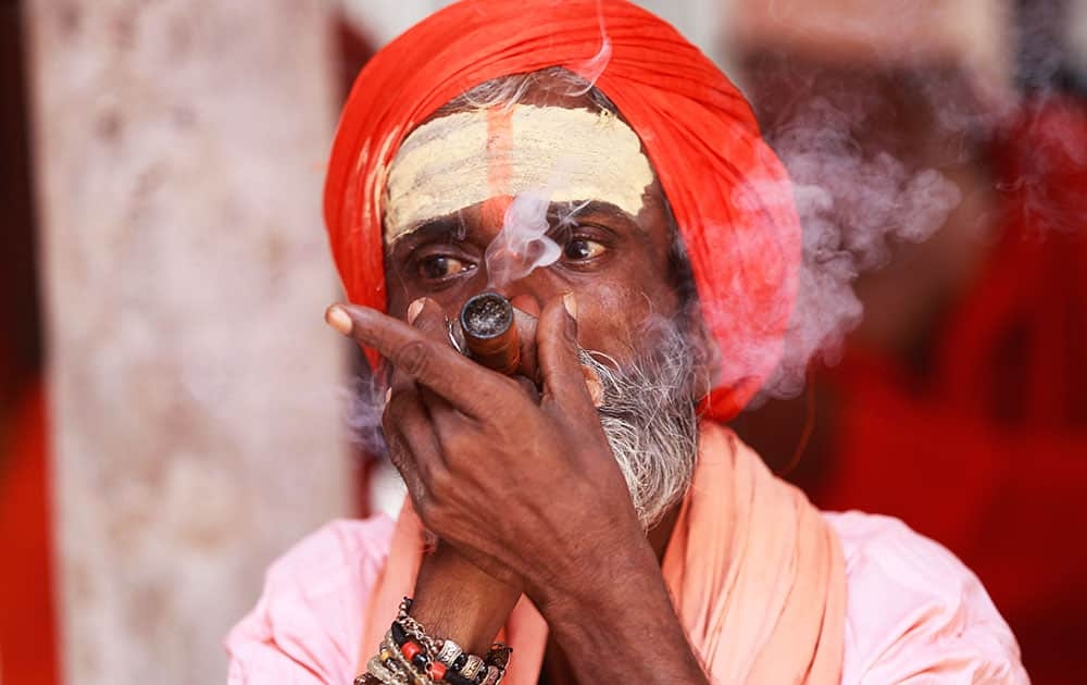 A Sadhu smokes as he waits to register for the annual Amarnath pilgrimage