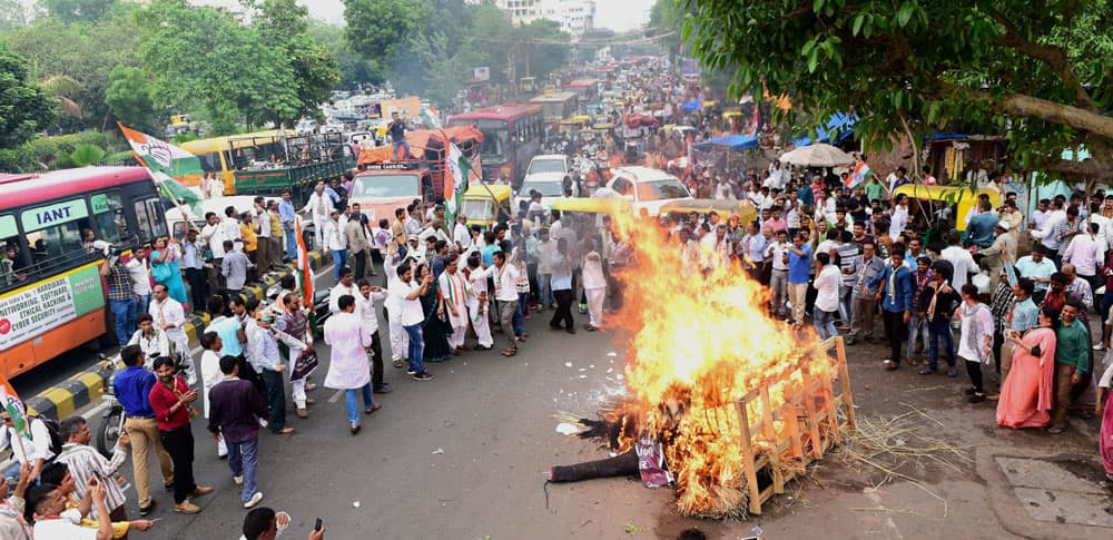 Activists and supporters of Congress party burn an affegy of inflation