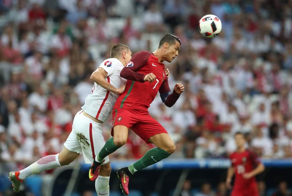 Cristiano Ronaldo, right, heads a ball next to Poland's Artur Jedrzejczyk